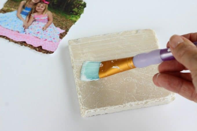 Paint the surface of the tile with Modge Podge