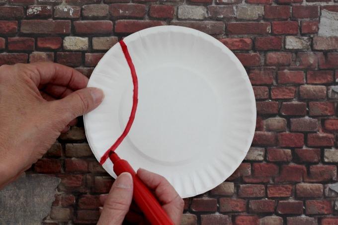 Transform paper plates into baseballs for easy baseball party decor.