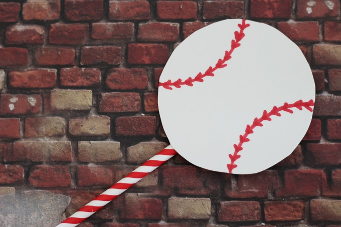 Add a straw to the baseball to stand it up.