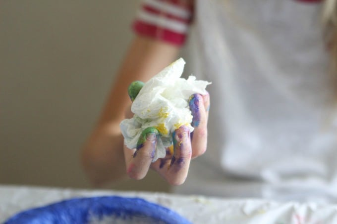 Painted hand holding paper towel