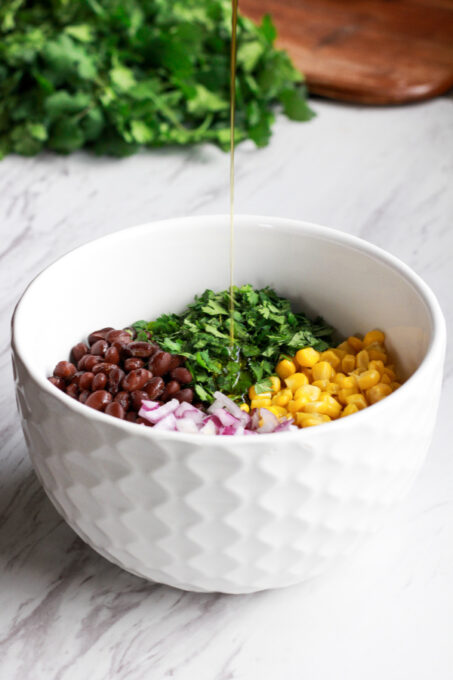 Pouring olive oil dressing to make black bean and corn salsa
