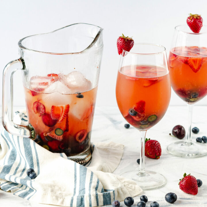 Red white and blueberry Sangria in pitcher and glasses
