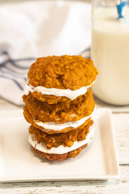 Pumpkin whoopie pies stacked on a white plate