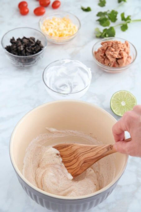 Mixing sour cream for seven layer dip cups