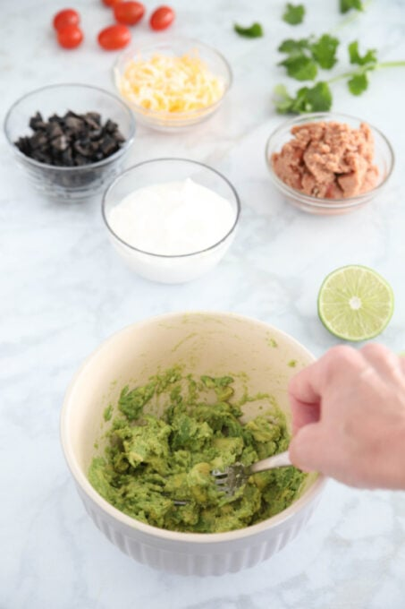 Making guacamole for seven layer dip cups