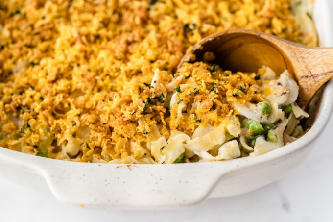 Serving tuna casserole with wooden spoon