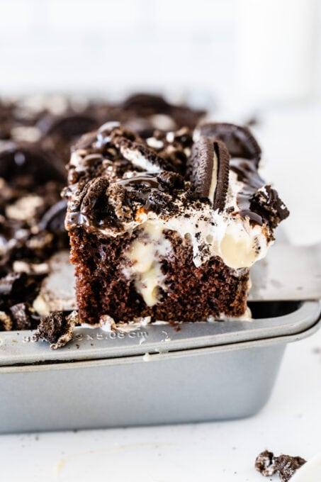 A slice of Oreo poke cake on a spatula