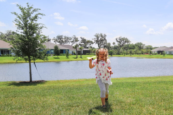 Girl playing with toilet paper roll butterfly in yard