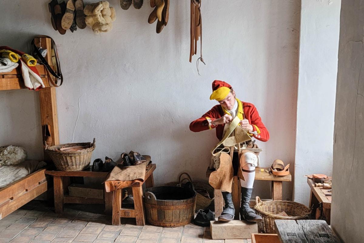 Shoemaker making shoes in an old fort bedroom
