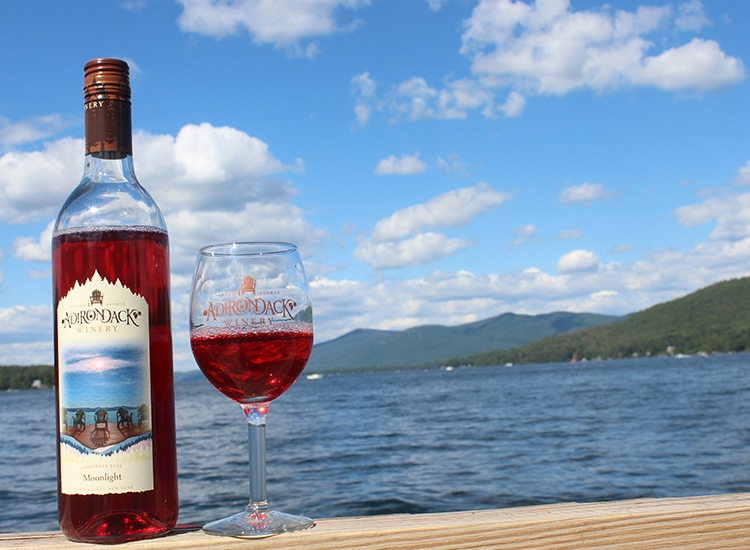Bottle of wine and a glass with a lake in the background