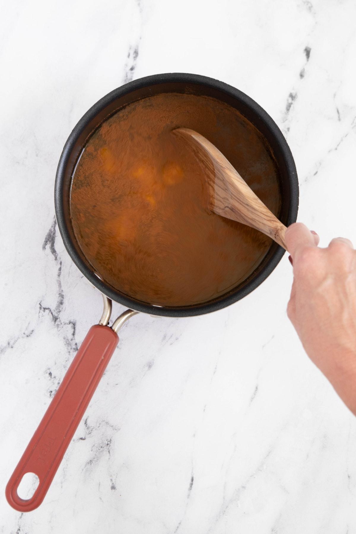 Stirring ingredients for pumpkin juice in saucepan
