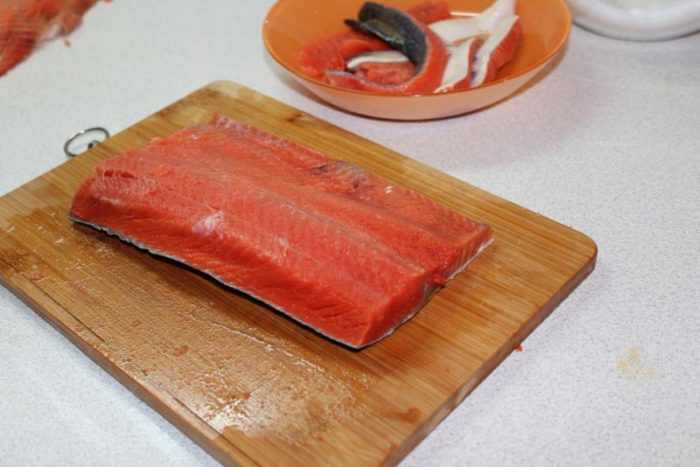 Χρησιμοποιήστε ένα κοφτερό μαχαίρι για να κάνετε μια βαθιά περικοπή κατά μήκος της πλάτης, κατά μήκος του πτερυγίου, και χωρίστε τα ψάρια σε δύο.