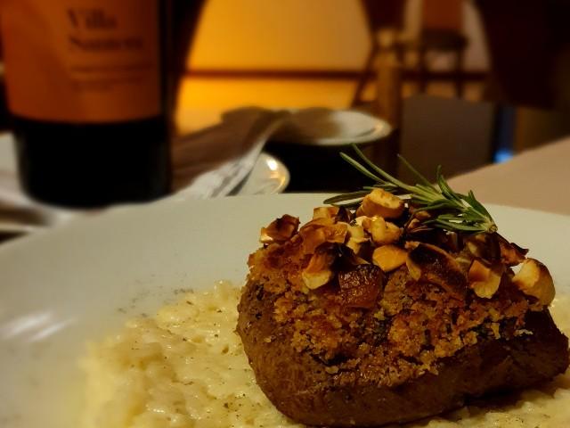 Imagem de um risoto com filé mignon e uma garrafa de vinho ao fundo.