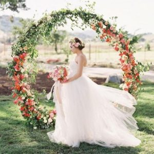 20 Trendy Summer Wedding Arches And Altars   HappyWedd com a giant circle wedding arch decorated with greenery and bold red blooms is  a trendy solution