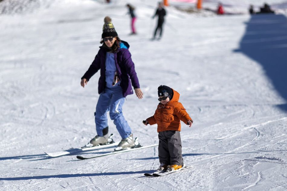Мама и малыш катаются на лыжах классического хода без лыжных палок на грнолыжном курорте