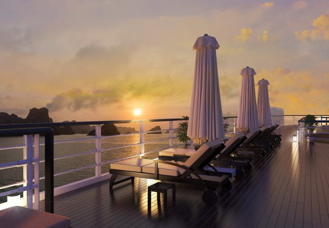 A halong sunset on the top deck with lounge chairs and closed parasols
