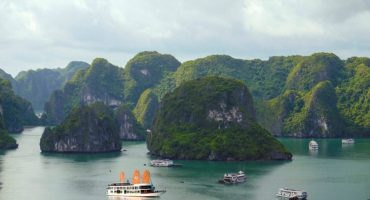Aerial shot of Halong with many small ships sailing between the islands