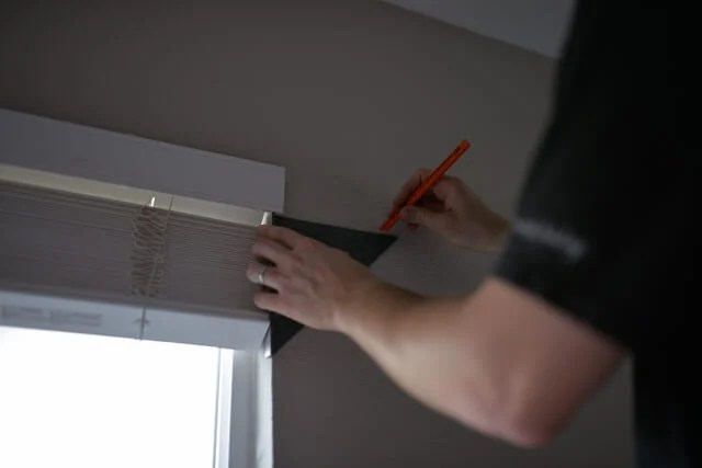 Man measuring place to hang curtains