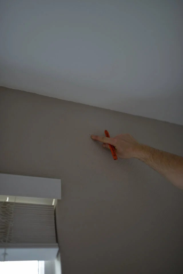 man marking spot with pencil where to hang curtains