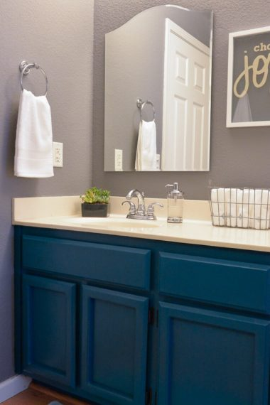 This makeover of a 1980s oak bathroom is stunning! Dark teal cabinets, modern lighting, and fun details make this bathroom makeover a showstopper.
