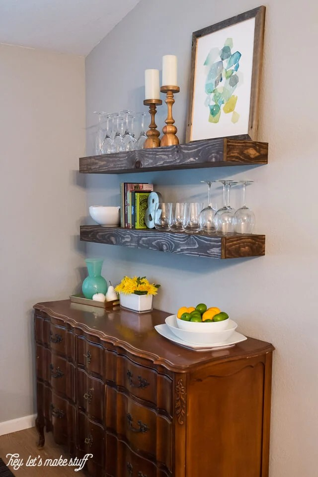 wooden floating shelves in kitchen with glasses and home decor and kitchen buffet below shelves