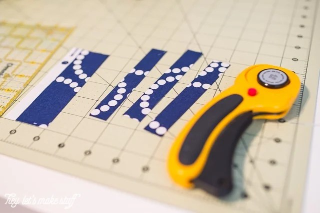 rotary cutter cutting fabric on sewing mat