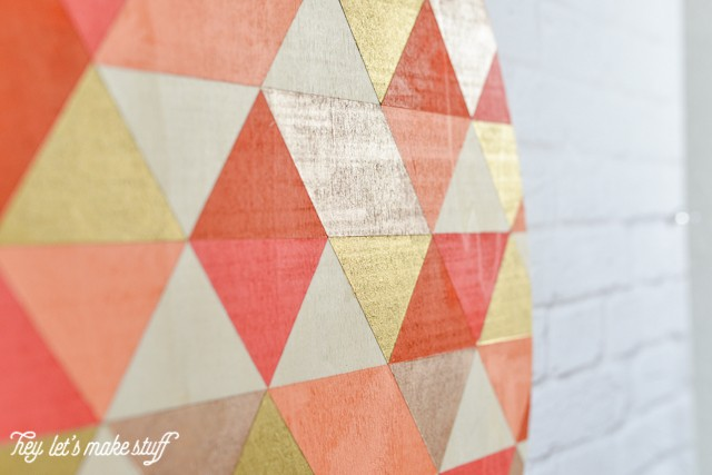side view of finished geometric painted pumpkin hanging on white brick fireplace