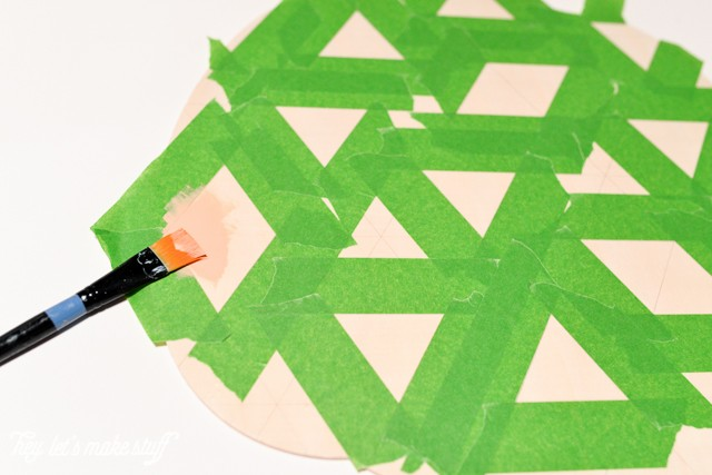 taped up grid lines to paint wooden pumpkin
