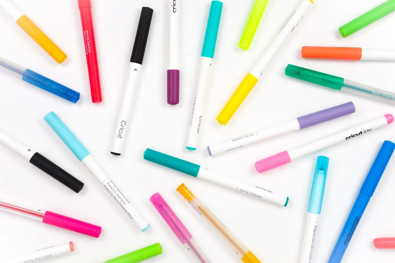 A bunch of Cricut pens arranged on a table.