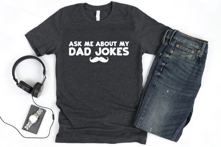 """Custom t-shirt using funny father's day svg file """"Ask me about my dad jokes"""" with headphones and jeans."""