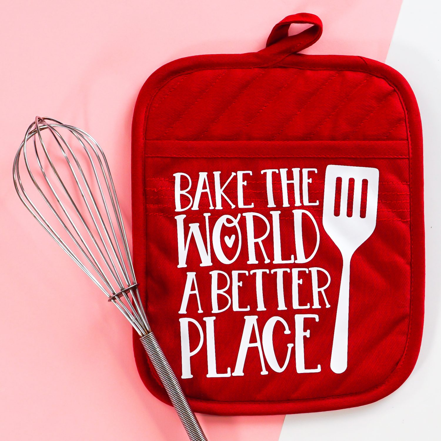 Finished customized pot holder on a pink and white background with a whisk.