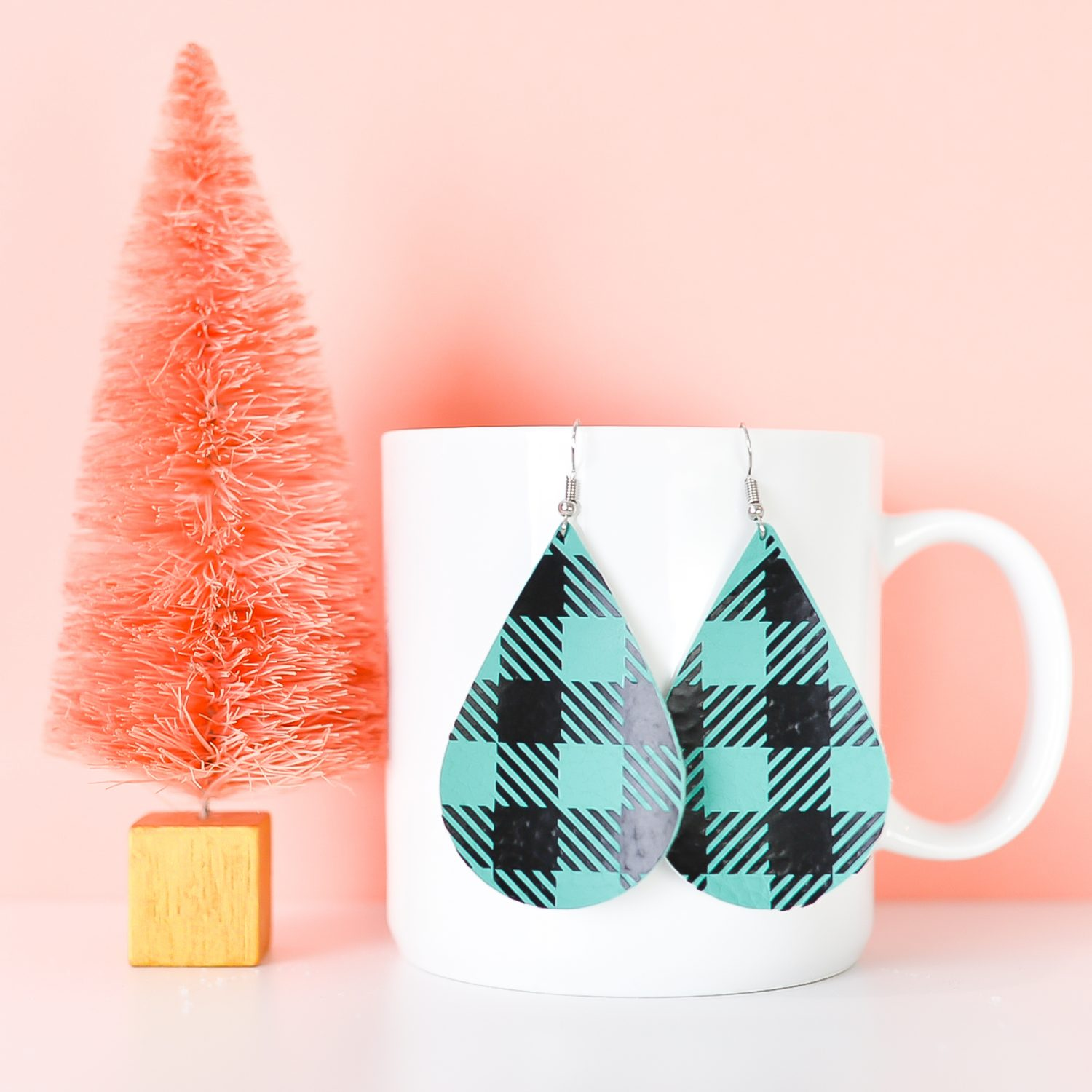 Finished teal buffalo plaid earrings hanging from a coffee cup