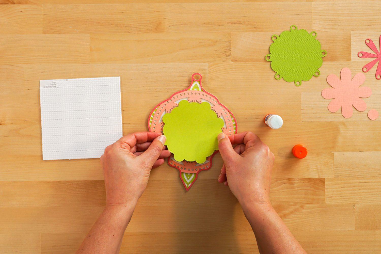 Hands placing layers for the Christmas mandala