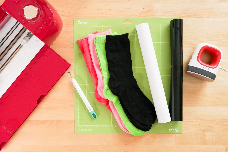 Supplies to make this project: Cricut, Cricut mat, socks, white HTV, black HTV, Cricut EasyPress Mini, weeding tool.