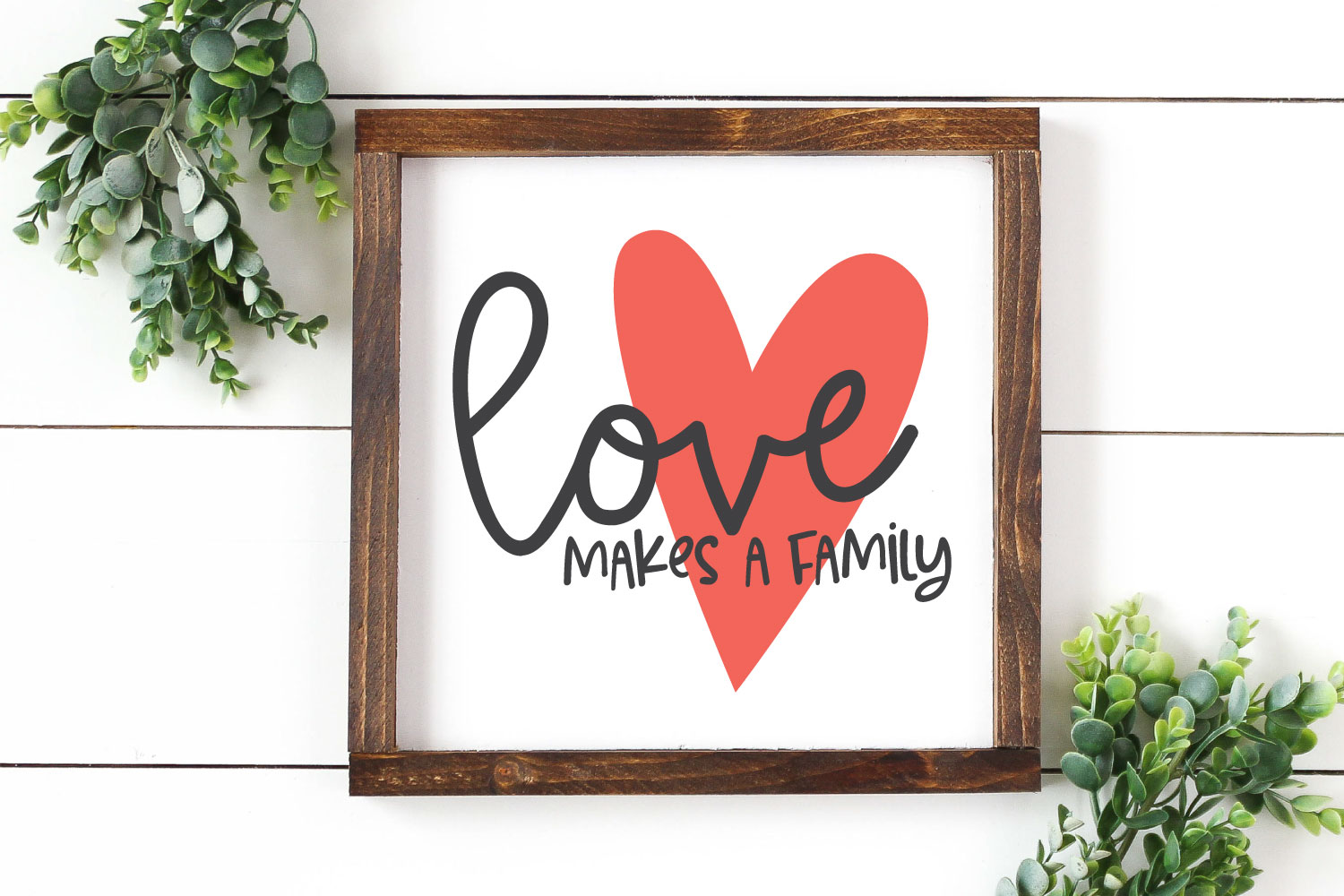Love Makes a Family SVG on home decor sign with greenery