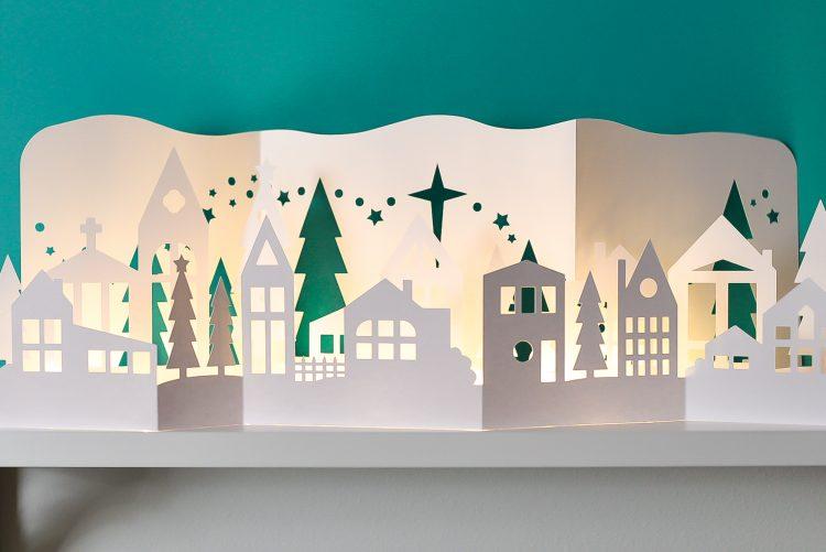 Papercut Christmas Village illuminated with fairy lights