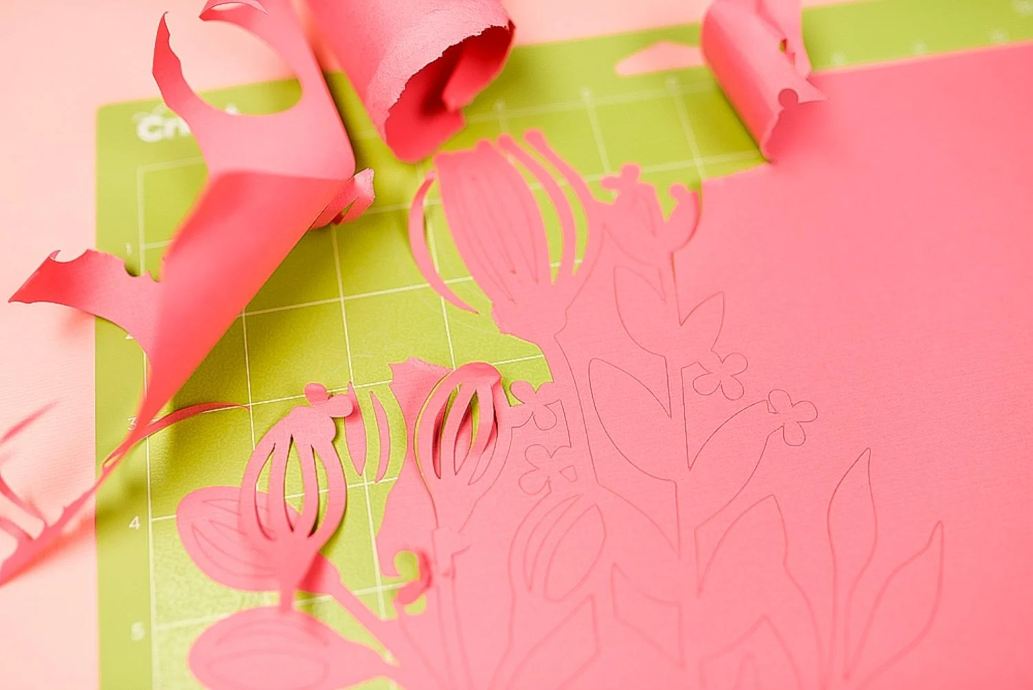 Cardstock ripped and torn off green cutting mat.