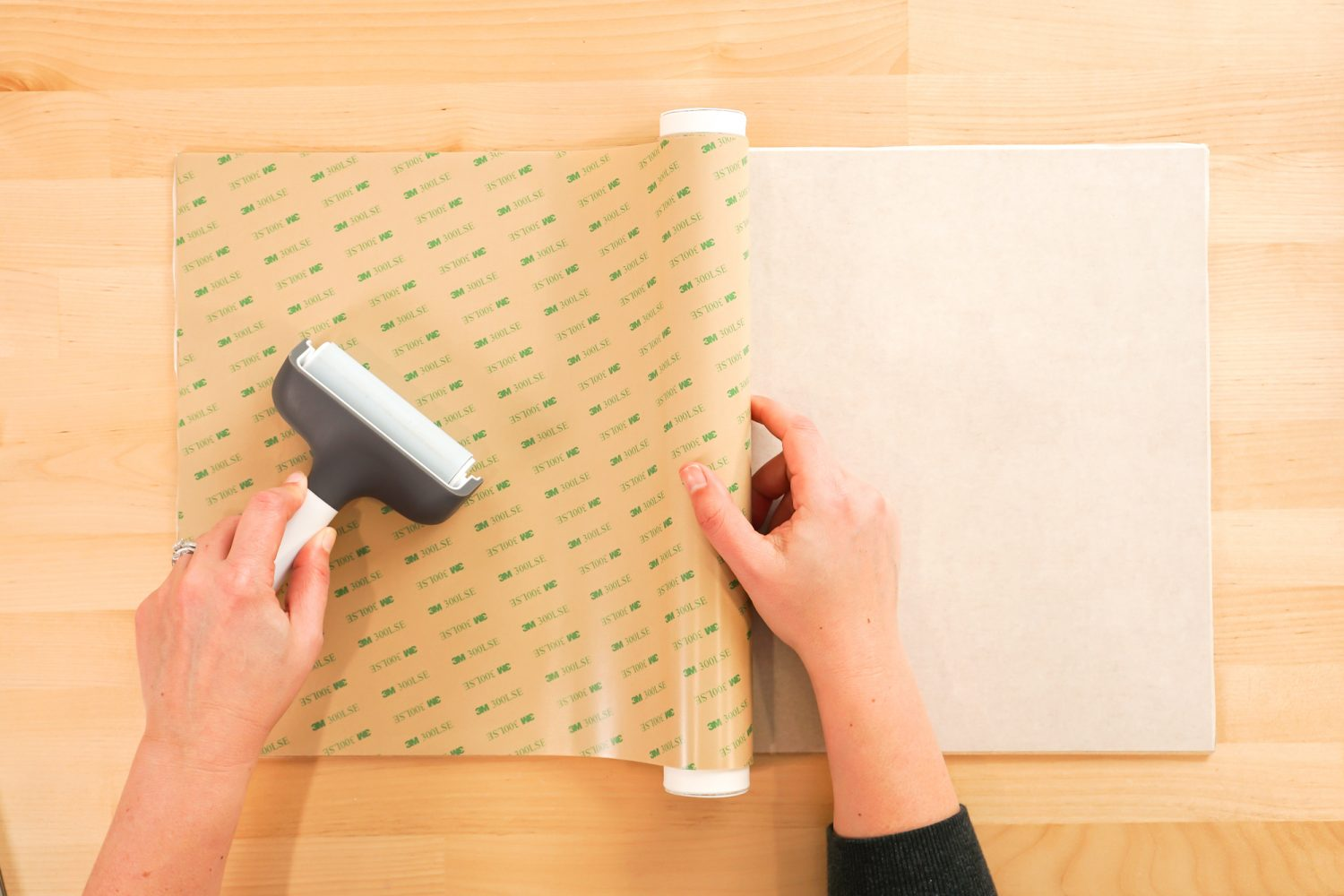 Hands using a brayer to apply the 3M adhesive