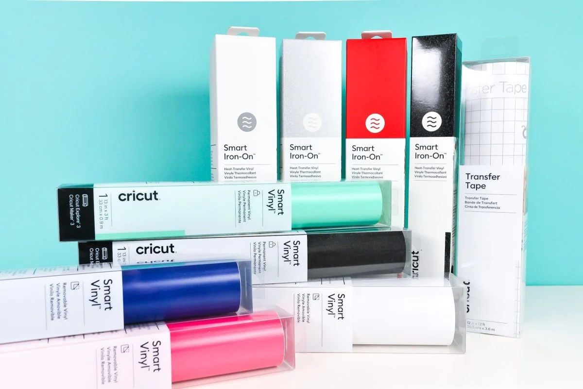 Stack of Smart Iron On, transfer tape, and Smart Vinyl in a variety of colors on a teal background.
