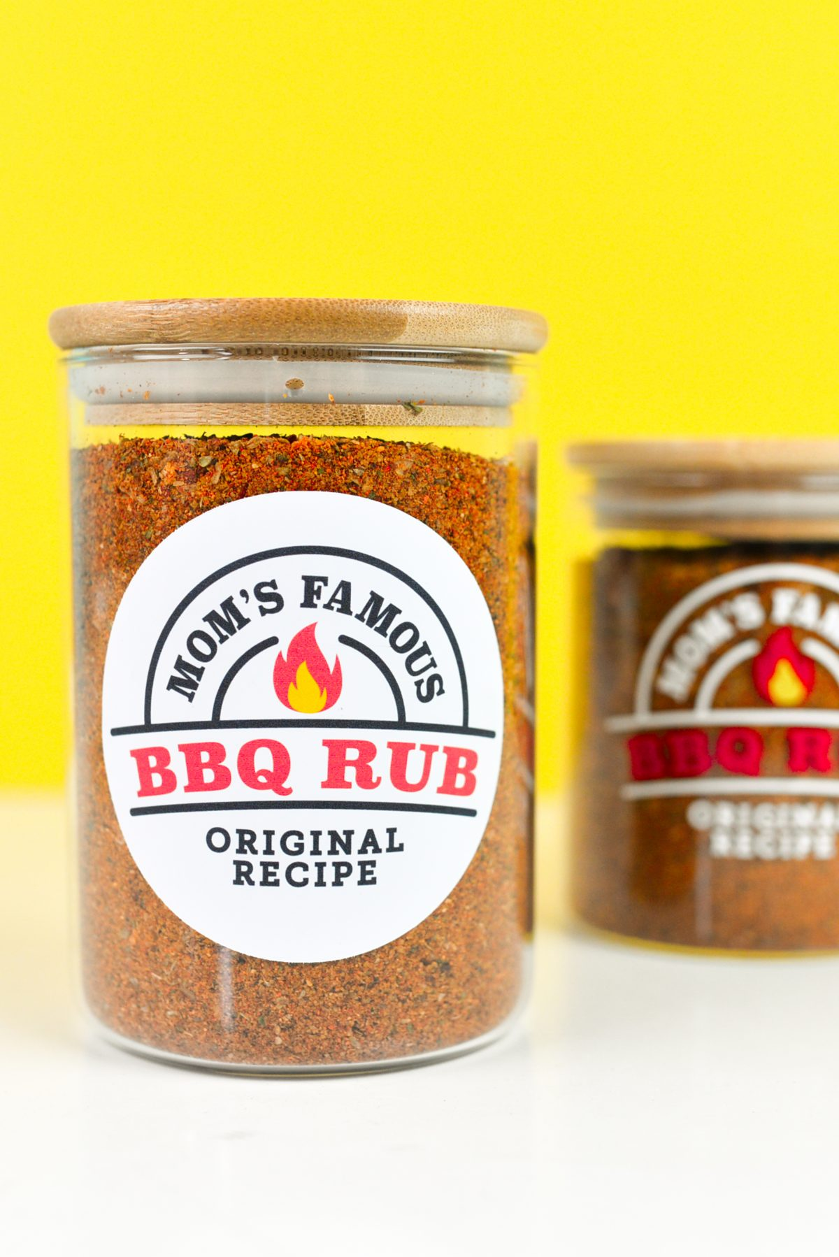 Two jars with two BBQ labels in front of a yellow background