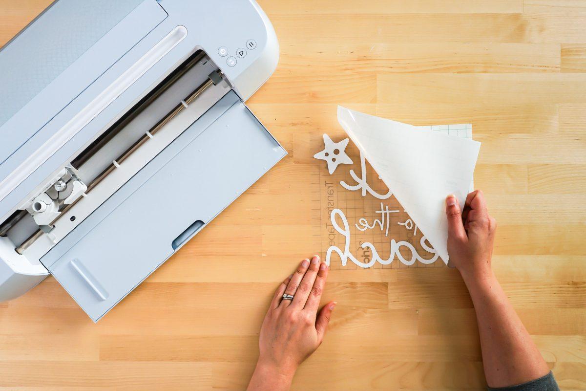 Hands peeling back carrier sheet on vinyl