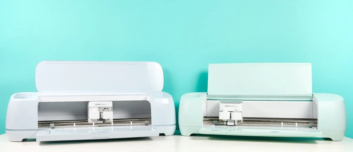 Cricut Maker 3 and Cricut Explore 3 on table with teal background