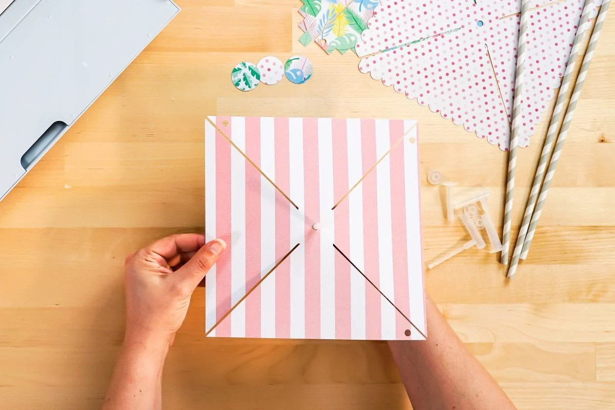 Hands placing paper pinwheel on pinwheel accessory