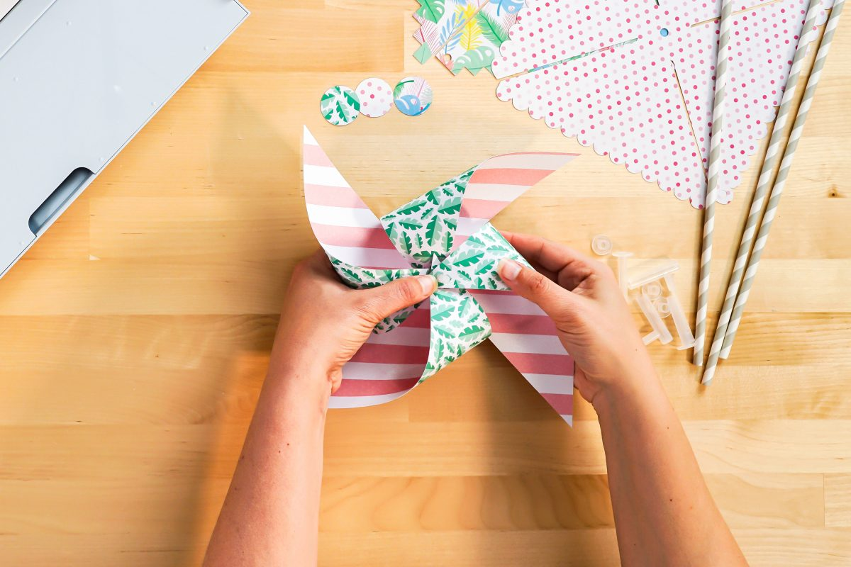 Hands folding pinwheel petals to form pinwheel.