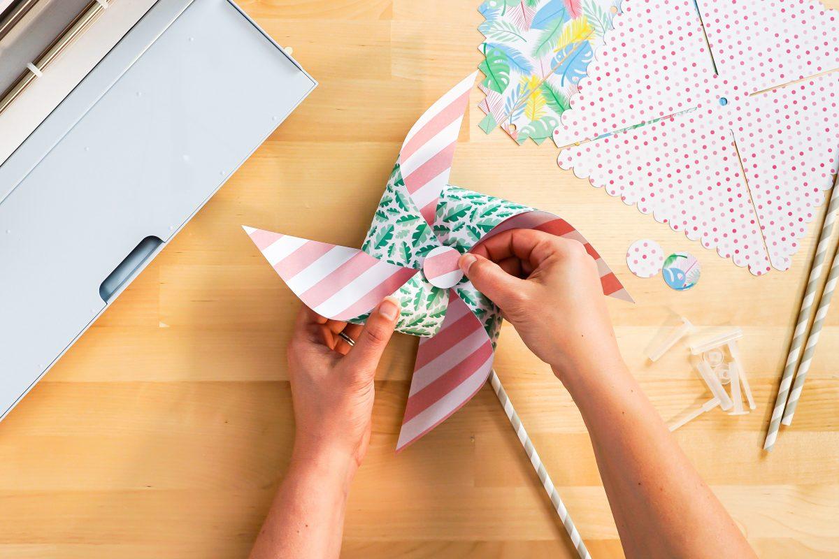 Hands gluing decorative circle onto pinwheel.