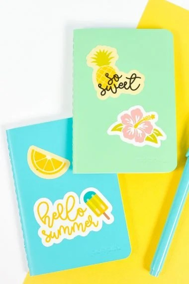 Blue and green notebooks with summer stickers on white and yellow background