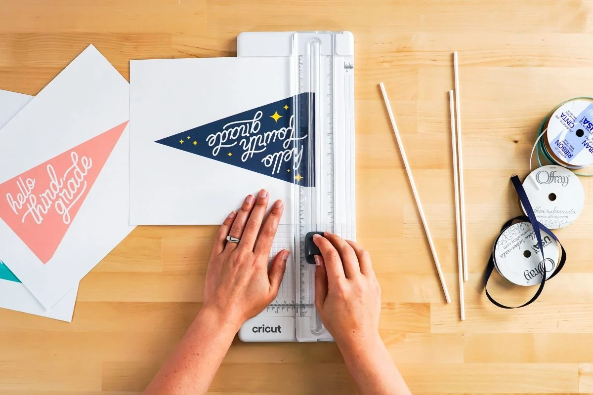 Hands using paper trimmer to cut flags.