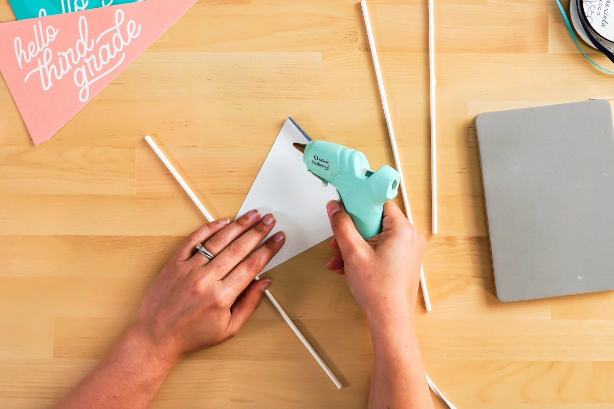 Hands using glue gun to glue pennant to dowel.