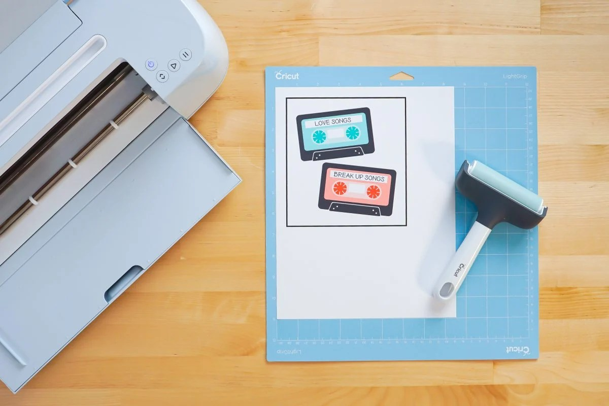 Overhead shot of printed mix tapes on a blue Cricut mat with a Cricut Maker 3 and brayer.