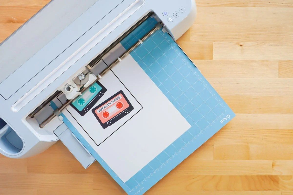 Overhead shot of Cricut Maker 3 with blue mat and printed mix tapes loaded.